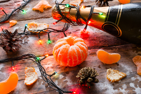 popping cork: New Year symbols - a bottle of champagne with a garland and tangerines