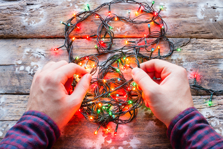 man unravels garlands on a wooden background