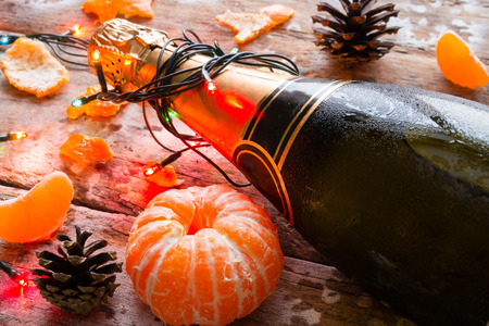 popping cork: chilled bottle of champagne with garland closeup and tangerines on a wooden background