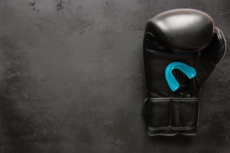 padding: One boxing glove and a mouth guard on a black background with space for text