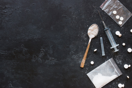 Drugs in the form of powder and tablets, a spoon and a syringe on a black background mockup
