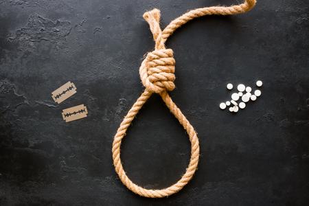 methoden van zelfmoord - touw schuifknoop, messen, pillen op een zwarte achtergrond