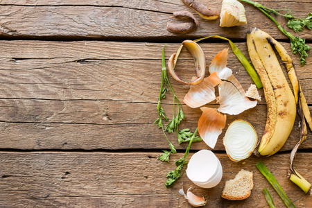 Food waste on a wooden background with space for text