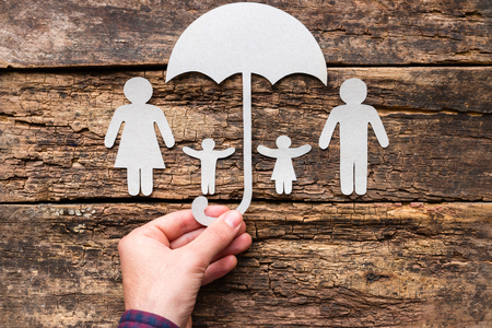 A man holds an umbrella over his family - a concept of protection and insurance