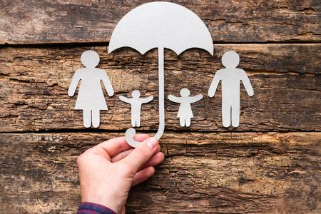 Mężczyzna trzyma parasol nad swoją rodziną - pojęcie ochrony i ubezpieczenia