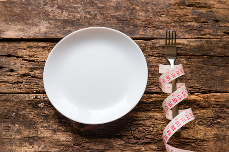 empty plate and fork wrapped with a measuring tape on a wooden background