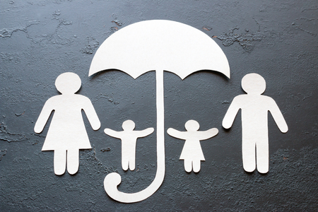 paper family under an umbrella on a black background concept caring, insurance