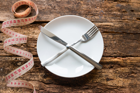 knife and fork lie in the shape of a cross on a plate and measuring tape on a wooden background concept diet