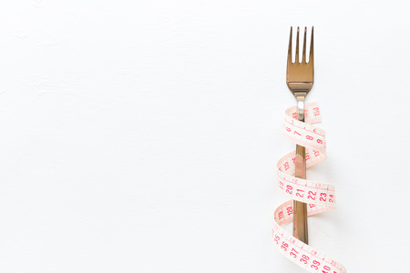 fork wrapped in a measuring tape on a white background with place for text concept diet