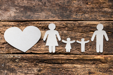 paper family and heart on a wooden background