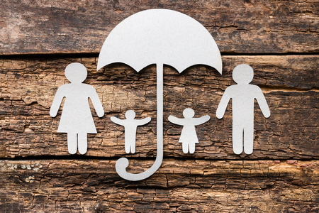 paper silhouettes of the family in which the children are under an umbrella. concept of insurance