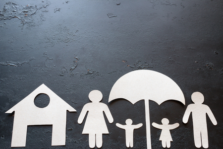 paper family with children under an umbrella on a black background with space for text