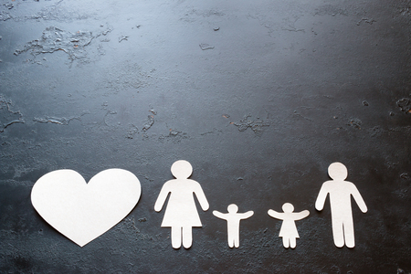 paper family and heart on a black background with space for text