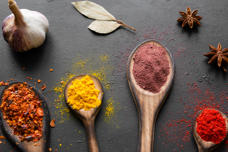 Spoons with spices, herbs and seasonings on a black background Standard-Bild
