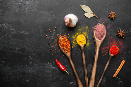 Spoons with spices, herbs and seasonings on a black background mockup Standard-Bild