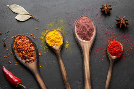 spices and condiments in spoons on a black background Standard-Bild