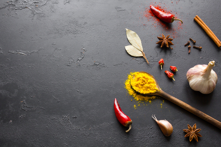 spices and herbs for cooking on a black background with space for text