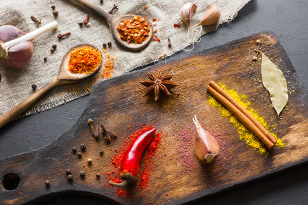 Spices and herbs for cooking on a cutting board and in wooden spoons