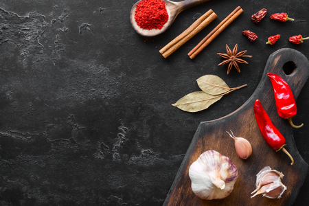 cutting board with spices and herbs on a black background and space for text Standard-Bild
