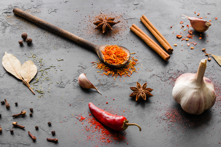 different spices and seasonings with herbs on a black background