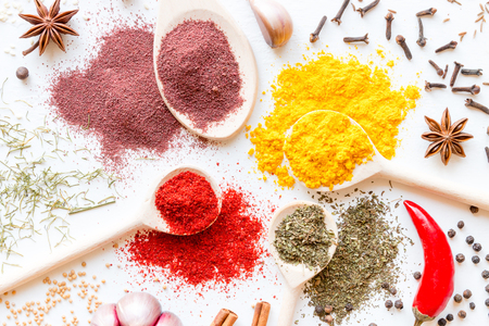 a variety of herbs and spices for cooking on a white background