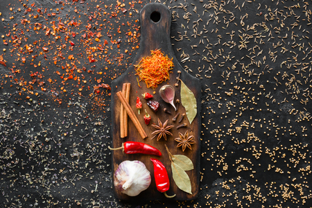 seasonings and herbs on a cutting board and spices on a black background
