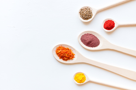 Spoons with different spices on a white background with place for text