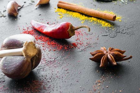 garlic, pepper and other spices close-up on a black background Standard-Bild