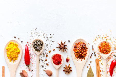 Spoons with condiments and spices on a white background with space for text