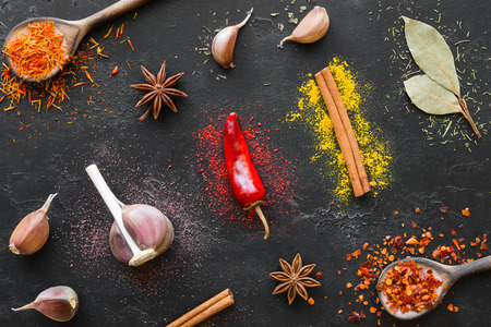 pepper, garlic, cinnamon and other spices and seasonings on a black background