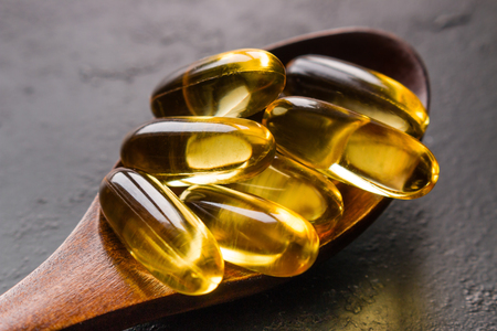 wooden spoon with capsules of fish oil close-up