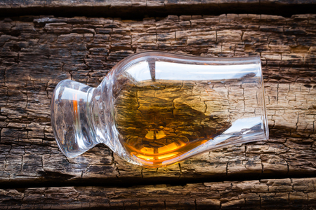 a glass of whiskey on a wooden background