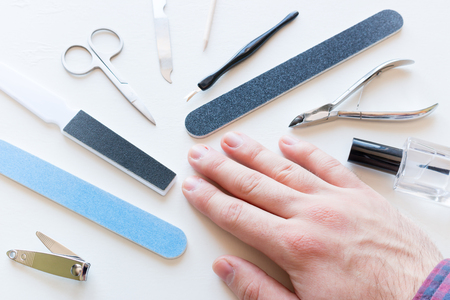 man with not well-groomed nails and tools for manicure Stock Photo