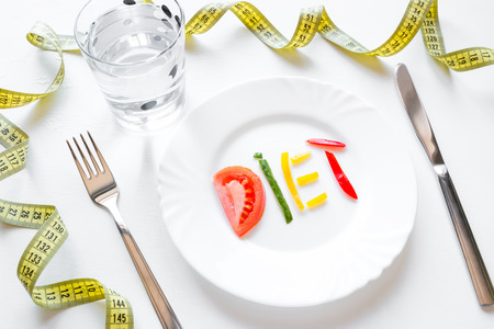 diet concept dish with vegetables, cutlery and measuring tape
