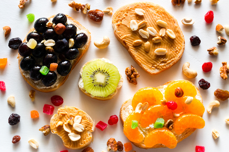 homemade cooked sandwiches with fruits and berries on a background of nuts and dried fruits close-up