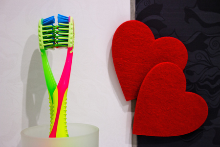 toothbrushes on the background of hearts concept world day of kissing