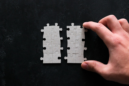 business concept hand connects puzzle pieces on black background Stock Photo