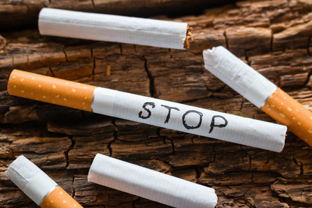 word stop on a cigarette and broken cigarettes. stop smoking concept Stock Photo