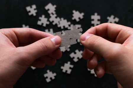 man holding two matching puzzle pieces on black background