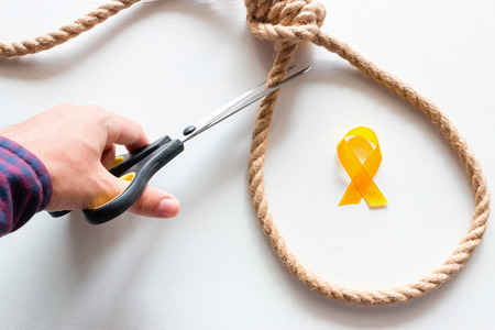 cuts the noose. yellow ribbon symbol of stop suicide Stock Photo