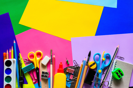 school supplies for study on a multi-colored background with space for text