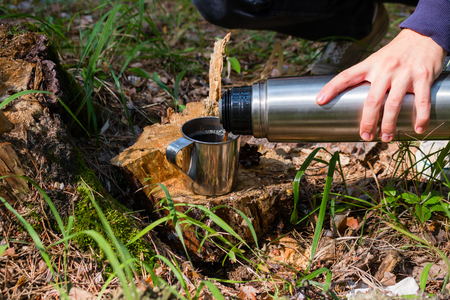 hiker pours tea from a flask in a summer forest Stock Photo