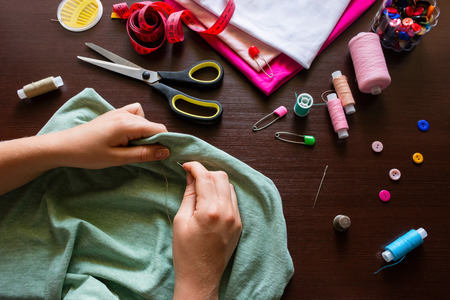 seamstress holds a needle and thread sews clothes