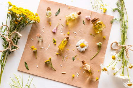 wild flowers and a bottle of natural cosmetics on a white background Stock Photo