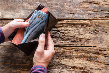 man with a purse with money on a wooden background with space for text Stock Photo