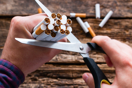 smoker cuts a cigarette with scissors. stop smoking cigarettes concept