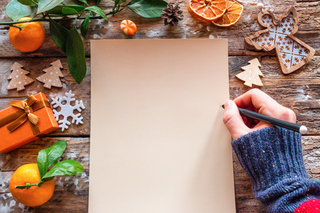 writes a Christmas letter with a wish list for the new year on a wooden background template