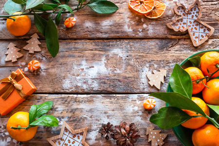 tangerines and Christmas-tree decorations on a wooden background with a place for text.