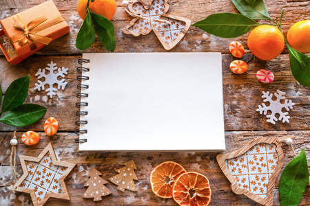 empty list of wishes and frame from Christmas decorations and tangerine on a wooden background Stock Photo