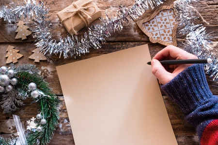 Writing a wish list Christmas letter on a wooden background with decorations